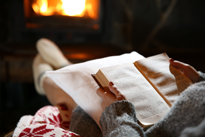 Woman resting with book near fireplace