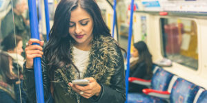 Let's talk about British Indian coming out stories. Image of an Indian woman in a London tube looking at her mobile.